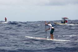 Champion Connor Baxter and Dave Kalama exchange leads as escort boat trails paddlers in the middle of the Molokai Channel