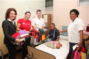 P&O Cruises and Save the Children staff give passenger knit blankets to a Vanuatu hospital