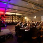 2 - Guest MC and Auctioneer Brendan Quill addresses guests seated in the winery Barrel Hall_media