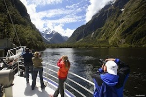 32004TS00: Tourists photographing on deck of cruise boat in Harrison Cove, Milford Sound, Fiordland National Park. Mount (Mt) Pembroke behind (2015masl). Milford Sound, Fiordland National Park, Southland Dist., NZ