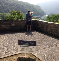 Tourist enjoy a scenic view marked by a #TakeOnPocono sign