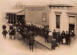 A CROWD gathers to watch as police gather gold (in boxes on footpath) in 1850s. (Museum of Victoria.)