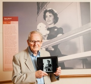 "Ship photographer Dick Dawson poses in front of an image of Elizabeth Taylor whom he captured during one of the legendary film star's many travels aboard Cunard Line. The image is also shown on Dawson's iPad while he recently toured  the interactive ""Stars Aboard"" exhibit featured on flagship Queen Mary 2."