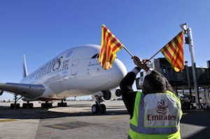Ground staff ushering in the double-decker aircraft at Barcelona-El Prat Airport.