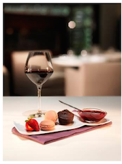 "A Vin Gourmand: a glass of red wine and an  assortment of ""grignotises"