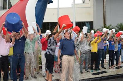 In this photo provided by Carnival Cruise Lines, Yvette Sanchez, left, pours ice water down the back of Carnival Cruise Lines' CEO Gerry Cahill, second from left, as he joined more than three dozen other Carnival employees for the ALS Ice Bucket ...