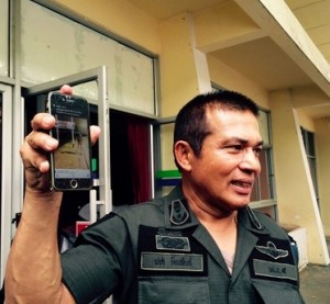 Police Major General Pacha Rattapan holding up an image of the naked man on his mobile phone