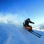 A male skier turning in deep powder with mountains valley's and blue sky in the back ground