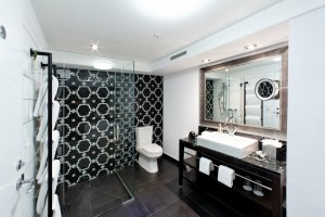A guest room featuring a walk-in shower and a striking mosaic wall designed by Stewart Harris of MacIntosh Harris_media