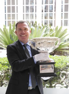 AccorHotels chief operating officer Simon McGrath wears white gloves to lift Australian Open trophy cup