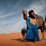 A Berber guide with his camel in the Sahara desert, Morocco_ a scene tha...