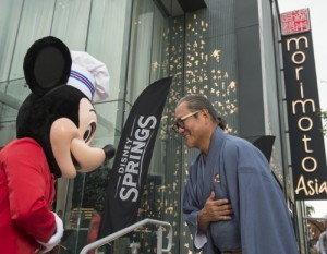 Mickey Mouse and Chef Masaharu Morimoto bow in celebration of the opening of Morimoto Asia Sept. 29, 2015 at the newly named Disney Springs complex at Walt Disney World Resort in Lake Buena Vista, Fla. Re-imagined from Downtown Disney, Disney Springs is doubling the number of shopping, dining and entertainment experiences opening in phases through 2016. (David Roark, photographer). (PRNewsFoto/Walt Disney World Resort)