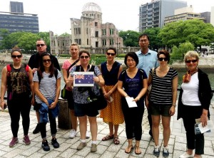 TravelManagers' Jennifer Jones (holding flag) and Sheri Foreman (far right) with their famil group, pictured in front of the Hiroshima Peace Memorial (Genbaku Dome)