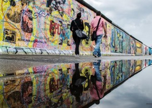 epaselect epa04304896 A woman and a man walk along the painted East Side Gallery, a former part of the Berlin Wall, and are reflected in a rain puddle in Berlin, Germany, 08 July 2014. The weather forecast predicts more rain for the following days. EPA/PAUL ZINKEN