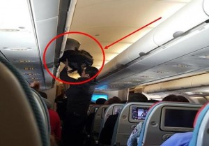 An image from a video clip taken by another passenger shows suspect apparently trying to interfere with the luggage of another passenger in an overhead compartment on the plane. (Photo released by Tourist Police at S