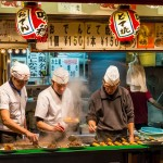 Men cook traditional Japanese street food on December 27, 2014 in Osaka, Japan.