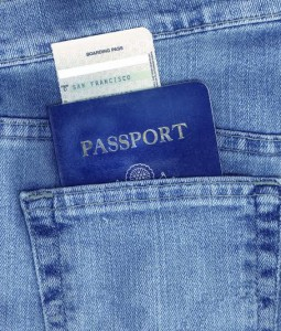 Passport and boarding pass in back pocket of blue jeans.