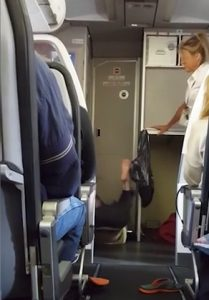 A flight attendant tries to calm the passenger, who is lying on her back by the cockpit and kicking her feet in the air