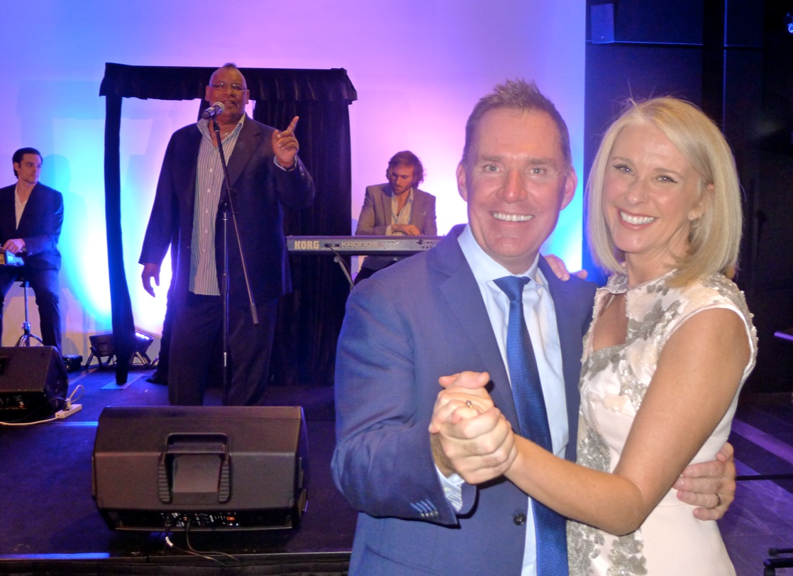 Accor chief Simon McGrath dances with travel journalist Tracey Spicer as the band plays on