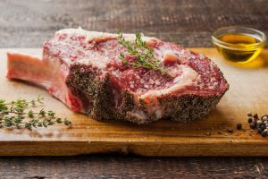 Tomahawk steak on the bone with thyme on cutting board horizontal