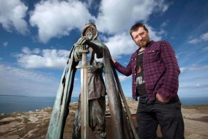 The new 'Gallos' sculpture at Tintagel Castle, with sculptor Rubin Eynon (English Heritage)