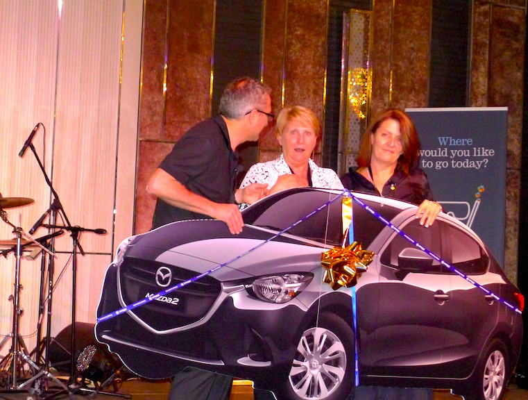 Vrrrm! Personal travel manaager Erin Morris is overwhelmed to win a new Mazda! From left- Michael Gazal, Erin Morris and Santina Notte Allianz Global Assistance