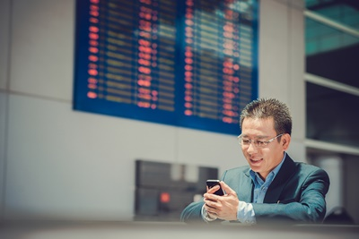 vietnamese-businessman-using-smartphone-at-airport-shutterstock_213739438