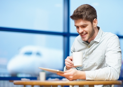 man-drinking-coffee-using-tablet-airport-4958-x-35